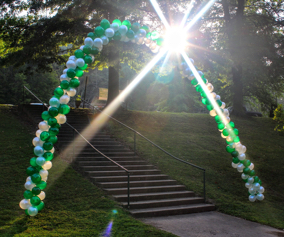 Welcome archway made of green and white balloons