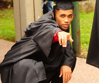 Salem University graduate in robe and cap, striking a proud pose